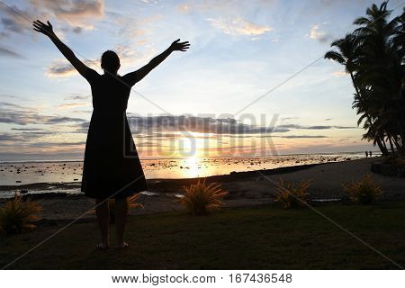 Silhouette of a tourist woman enjoys dramatic sunset on a beach in the Coral CoastViti Levu in Fiji. Travel concept Real peole copy space