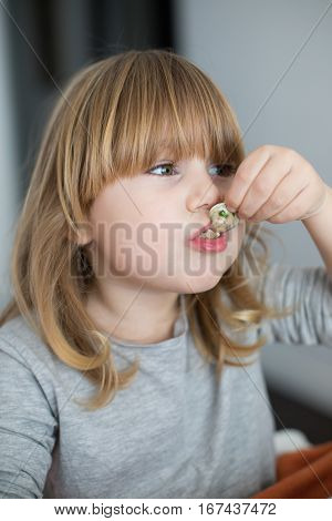 Child Sucking A Clam Looking