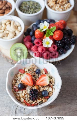 Paleo style breakfast: gluten free grain free oat free granola with mixed nuts and fresh berries and fruits selective focus