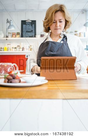 Portrait of confectioner at counter using tablet looking for recipe