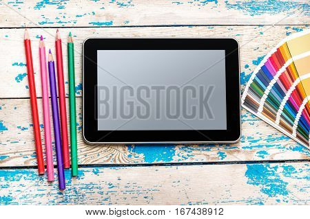 Tablet PC with color swatches book and colored pencils on wooden background.