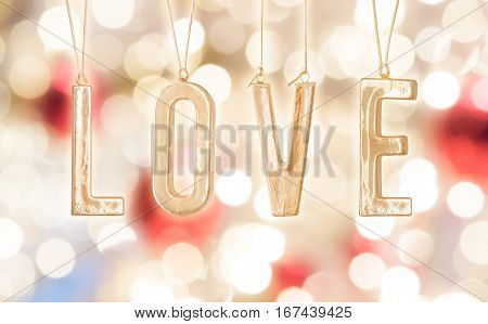 Golden Word love on bokeh blur of decoration red and white light background. Valentines Day love or wedding day concept.
