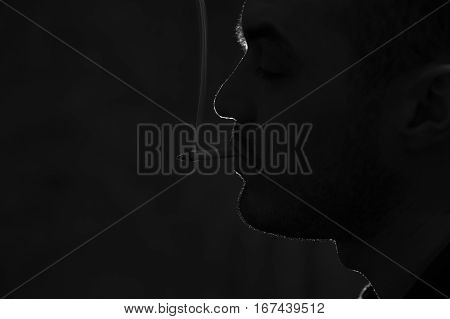 Portrait of young caucasian man smoking cigarette. Bad habits concept. Dark image