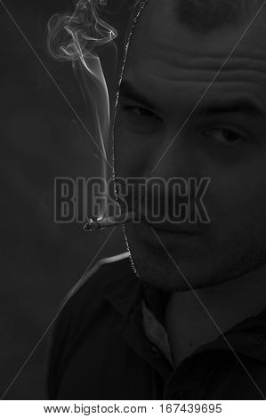 Portrait of young depressed man with cigarette. Bad habits concept. Black and white image