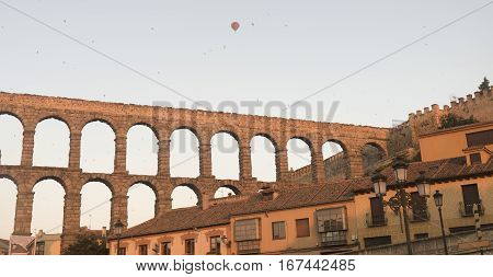 Segovia (Castilla y Leon Spain): the Roman aqueduct Unesco World Heritage Site at dawn with a colorful hot-air balloon