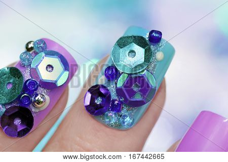 Colorful trendy purple blue manicure with nail art for beaded,rhinestone,sequin and sparkles closeup on female hand.