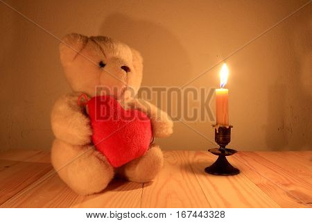 Teddy bear and red heart with candle light background sill life style