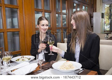 Business woman having a toast. Two beautiful woman drinking wine at the restaurant.