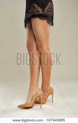 sexy legs girls in a beige shoes the hem of her black dress isolated on a beige background