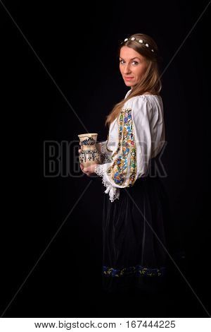 Closeup Of A Young Romanian Woman Dressed In Traditional Costume, Holding In His Hands A Cup Of Pain