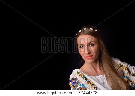 Closeup Of A Young Romanian Woman With Wreath Of Flowers On Head Dressed In Traditional Costume. Rom