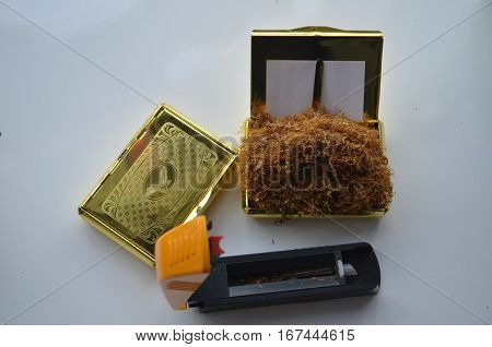 machine for filling cigarettes on the table with yellow lid and some tobacco in it and a snuffbox with tobacco in it