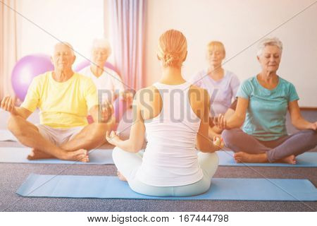 Instructor performing yoga with seniors during sports class