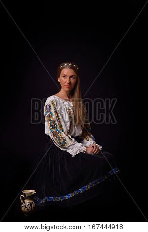 Closeup Of A Young Romanian Woman Dressed In Traditional Costume,sitting On A Chair With A Cup Of Pa