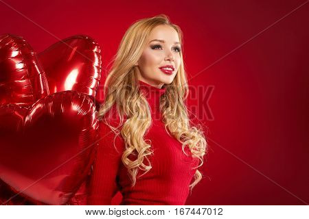 Beautiful blond woman posing on red . Valentine concept