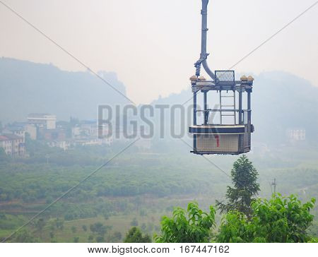 Photo of Empty Cable Car on Green Epic Scenery Background. Empty Cable Cabin on Ropeway on Green Landscape