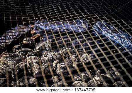 Hot coals on a barbecue with wire grid