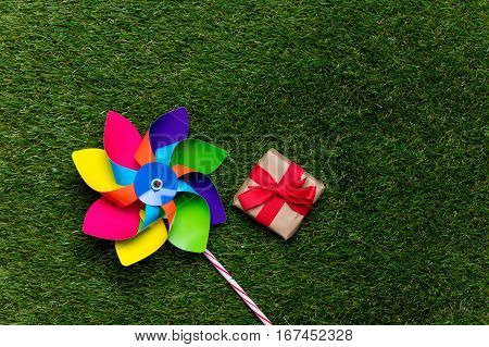 Multi Colored Pinwheel And Little Gift Box On Spring Green Glass Background, Above View