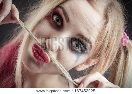 fun blond girl making fake mustache from her hair