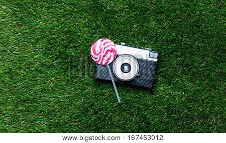 Vintage Camera And Lollipop Candy On Green Grass Background