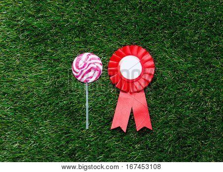 Red Reward And Lollipop On Green Grass Background