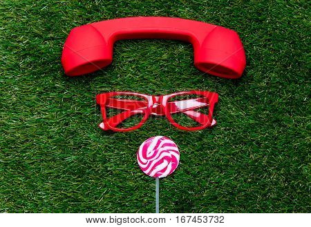Styled Red Glasses With Lollipop And Handset On Green Grass Background,