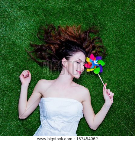Portrait Of A Young Redhead Woman With Pinwheel Lying Down On Green Spring Grass, Above Point Of Vie