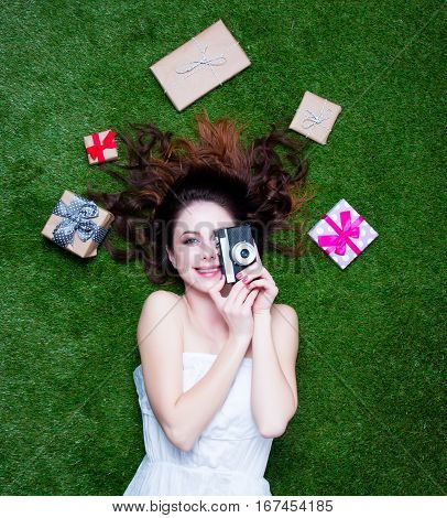 Portrait Of A Young Redhead Woman With Holiday Gifts And Camera