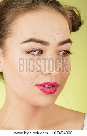 fun girl with bright makeup freckles on yellow background