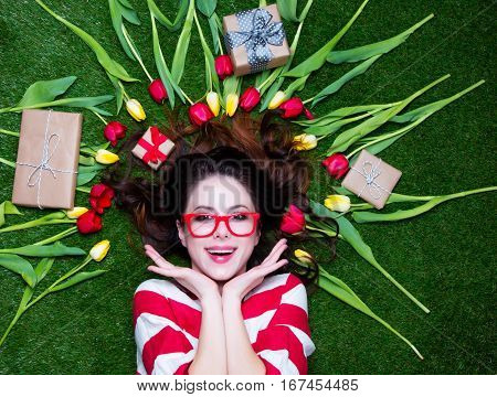 Portrait Of A Young Styled Redhead Woman With Tulips Around And Gift Boxes