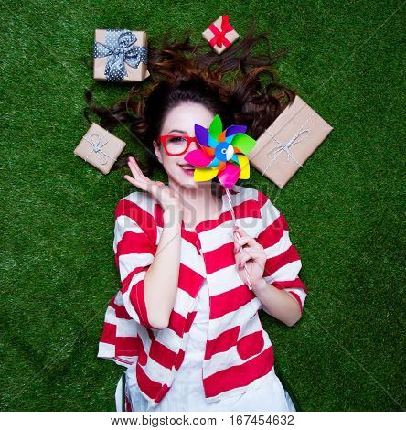 Portrait Of A Young Styled Redhead Woman With Pinwheel Toy Present Around Lying Down On Green Spring