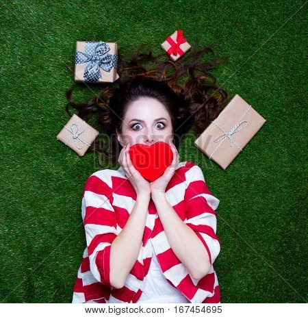 Portrait Of A Young Styled Redhead Woman With Heart Shape Gift And Present Around Lying Down On Gree
