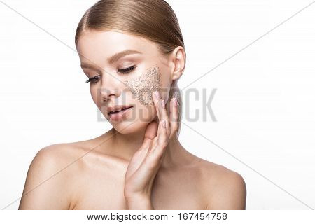 Beautiful young girl with scrub on the skin and French manicure. Beauty face. Picture taken in the studio on a white background.