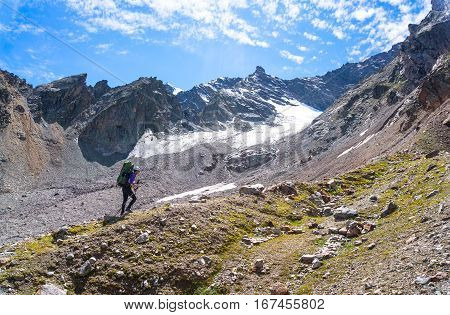 Young female tourist with a backpack on his back moving up the side of the mountain using trekking poles