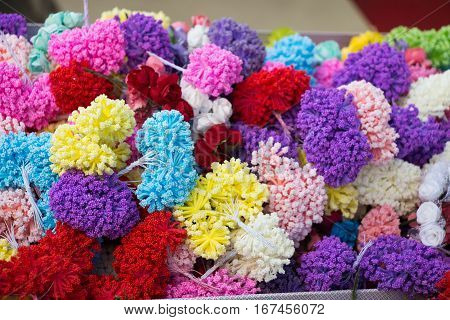 Set of different colours and shapes of pompoms in an open market