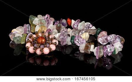 closeup brooch and beads from crystals of amethyst fluorite jasper carnelian and rose quartz on black table