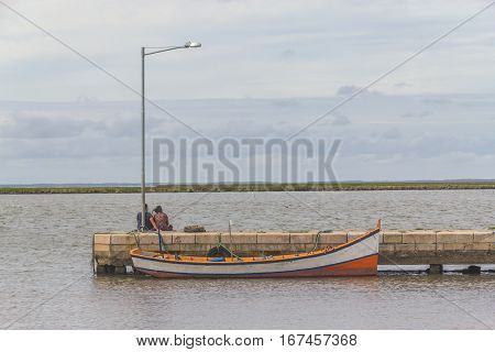 Couple sitting near of lagoa dos patos lake with boat in sunset