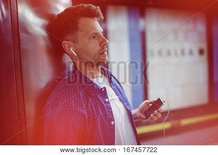 Man listening song while leaning on wall at railway platform