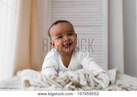 Laughing Baby Boy Lying On Tummy At Home