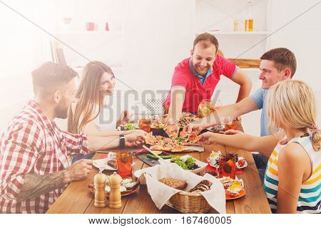 Happy friends eat pizza at festive table served for party. People celebrate with catering food on wooden table closeup. Women and men take the pieces of italian pizza.