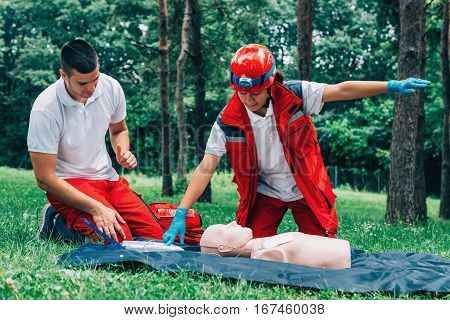 cpr training in park, green background, two people
