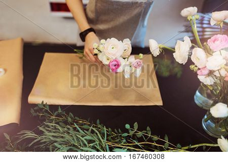 Top view of hands of female florist holding flowers for creating bouquet on black table