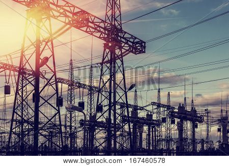 high-voltage power lines at sunset. electricity distribution station .