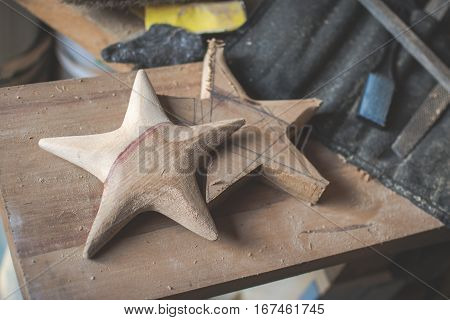 Dark toned photo of the workshop: making wooden stars from tulip tree; unfinished stars files sanding paper; selective focus