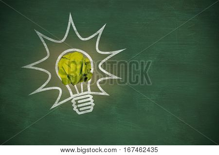 Digital image of crumpled paper ball against green chalkboard