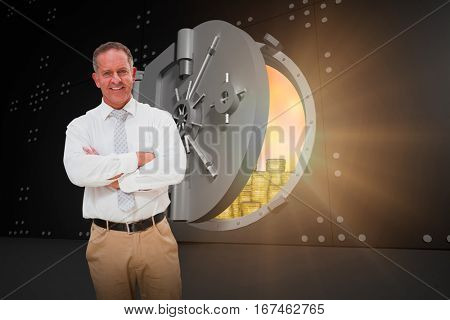 Smiling manager with arms crossed in warehouse against half opened safe