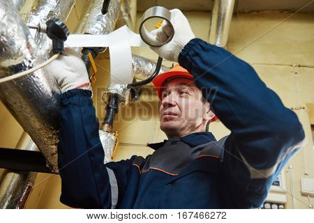Thermal insulation. worker insulating heating system pipes with foil