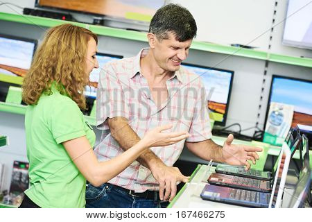 Seller assistant woman help purchaser choosing laptop computer