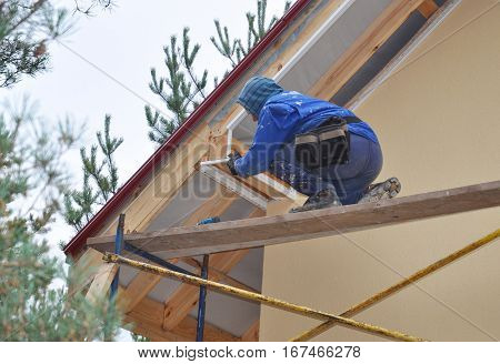 KYIV UKRAINE - February  14 2017:  Roofer on the Corner of House Install Soffit. Roofing Construction. Soffit is Usually Constructed of Vinyl Wood or Aluminum and is Installed on the Underside of Roof Overhangs and Eaves.