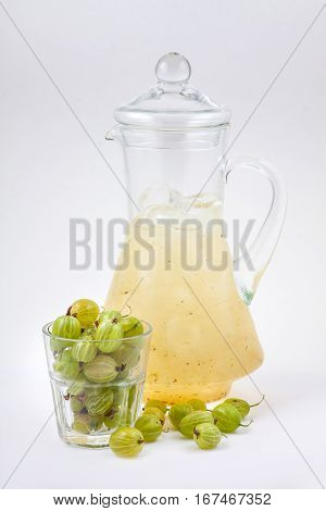 glass decanter with gooseberry juice and ice on a white background